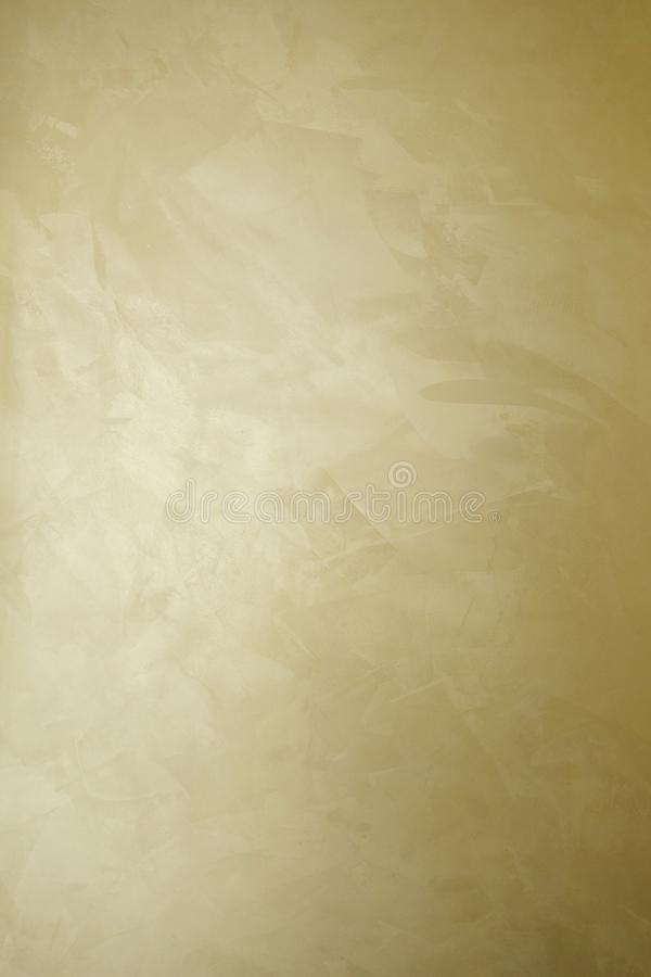 Golden decorative plaster texture with pearl glow. Vertical photo stock image