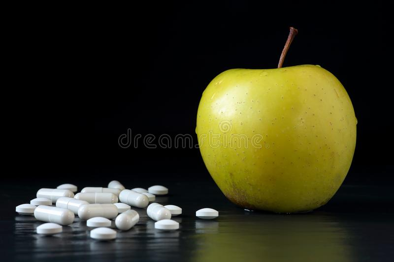 Golden delicious apple and different tablets and capsules on a black background with reflections. Health care, healthy eating and stock photos
