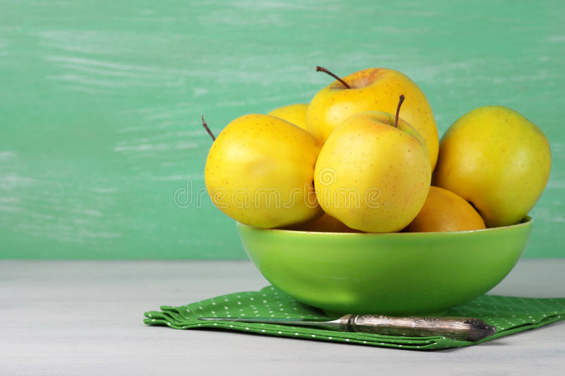 Golden Delicious apples. Yellow Golden Delicious apples in green bowl with napkin on rustic wooden background royalty free stock photos