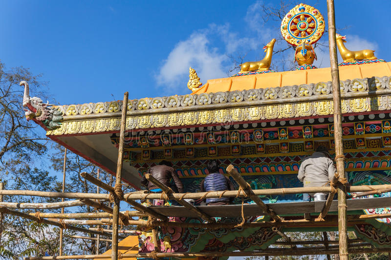 Golden Dharma wheel with deer in the top of entrance gate with construction site and workers of Guru Rinpoche Temple at Namchi. royalty free stock photo