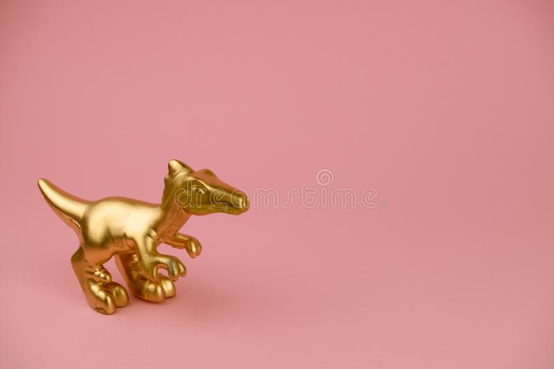 Dinosaur statuette on pastel pink background with copy space trendy minimal art card. Golden dinosaur statuette on pastel pink background with copy space trendy royalty free stock photo