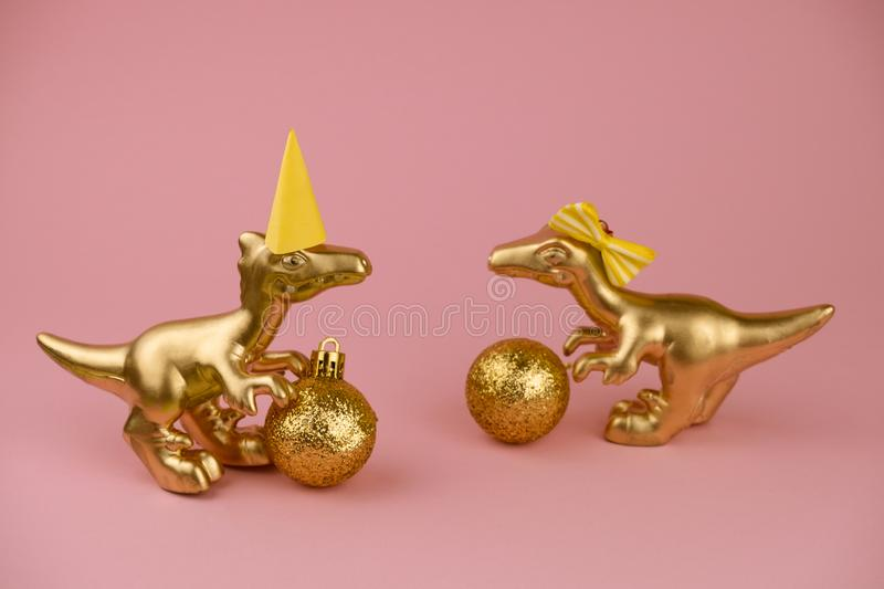 Dinosaur toys with golden christmas balls on a pastel pink background, trendy modern christmas card. Golden dinosaur toys with golden christmas balls on a pastel stock photography