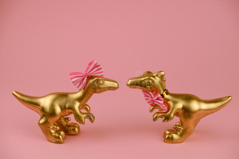 Dinosaurs toys boy in a bowtie and girl with pink hairpin bow standing together and looking to each other on a soft pink. Golden dinosaurs toys boy in a bowtie stock photos