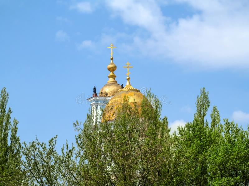 Golden domes with crosses of Savior-Transfiguration Cathedral behind the crowns of trees against blue sky Sumy, Ukraine. Old. Dome with shabby paint of an stock photos
