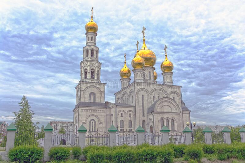 Golden domes of Savior Transfiguration Cathedral. Cathedral fenced by a stone fence. Russia, Abakan royalty free stock photography