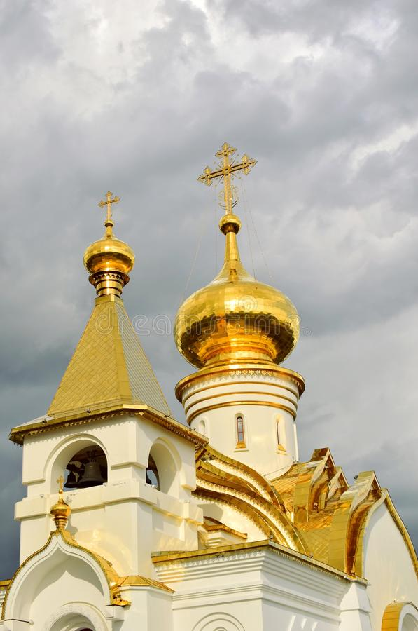 Golden domes of the white сhristian сhurch. White stone walls of the temple. Bright gilt domes. Stormy sky. Close up stock images
