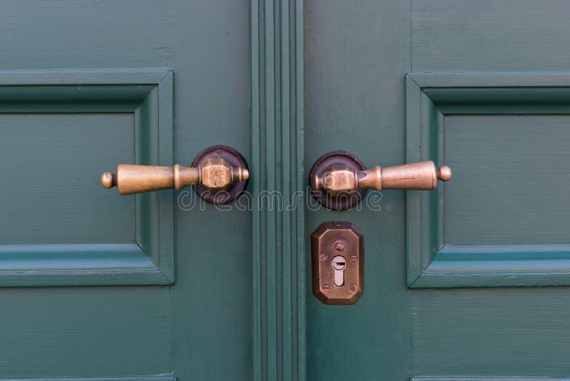 Golden door handles on green wooden doors. Old door handle stock images