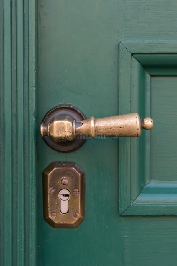 Golden door handles on green wooden doors. Old door handle royalty free stock image