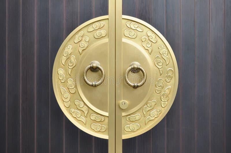 Golden Door knocker. On wooden door stock photos