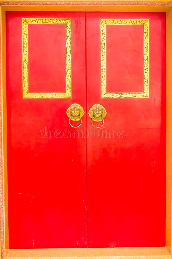 Golden door knocker in the shape of lion with ring on a red wooden door. Close up wooden Chinese style red door with lion head royalty free stock photos