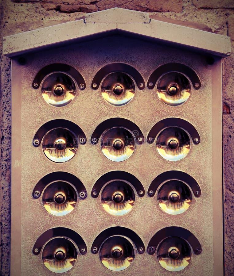 Golden doorbells in the old house with vintage effect. Many golden doorbells in the european house with vintage effect stock photo