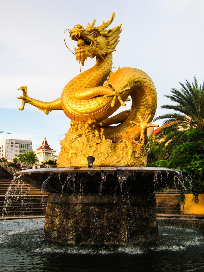 Golden Dragon, fountain in Phuket Thailand. A huge majestic sculpture of a mythical dragon cast in gold sit on a fountain in the town of Phuket in Asia royalty free stock photos