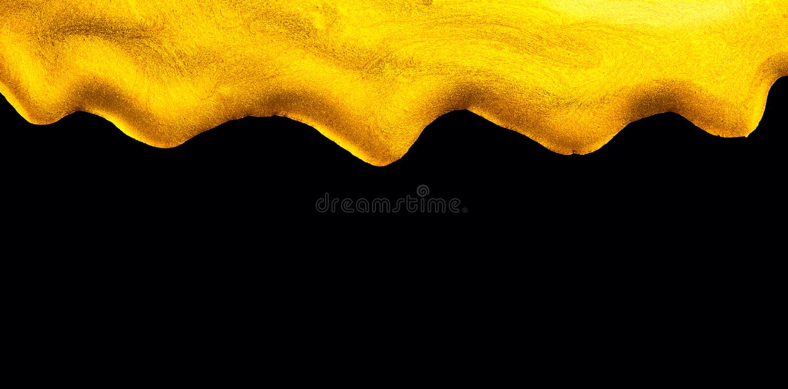 Golden dripping liquid paint texture, isolated on black background. Flowing abstract Gold metallic paint drops close-up stock photography