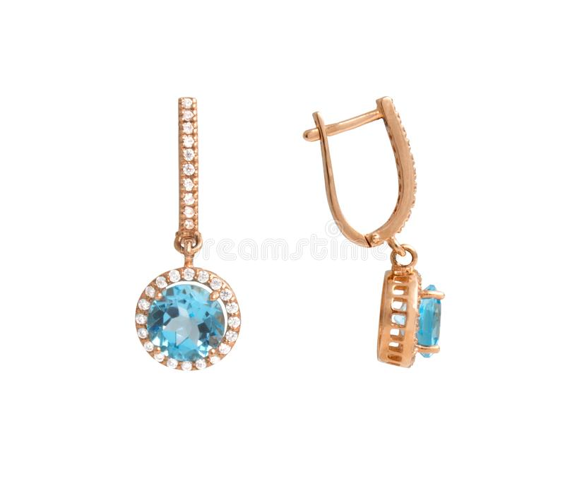 Golden earrings with blue gem - topaz and few diamonds royalty free stock images
