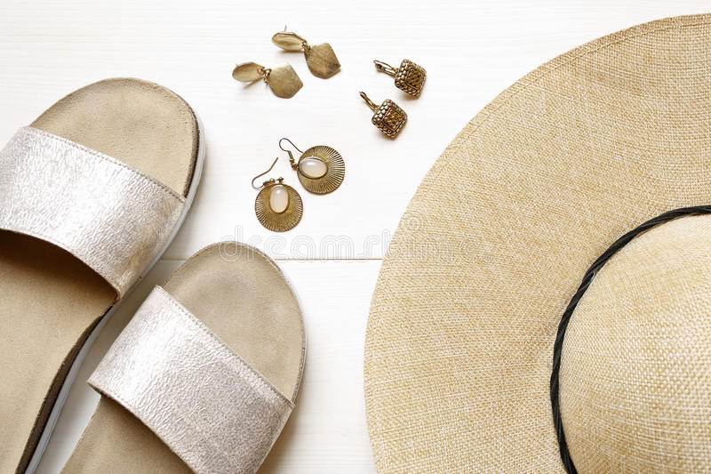 Golden earrings, straw hat, slippers- summer accessories royalty free stock image