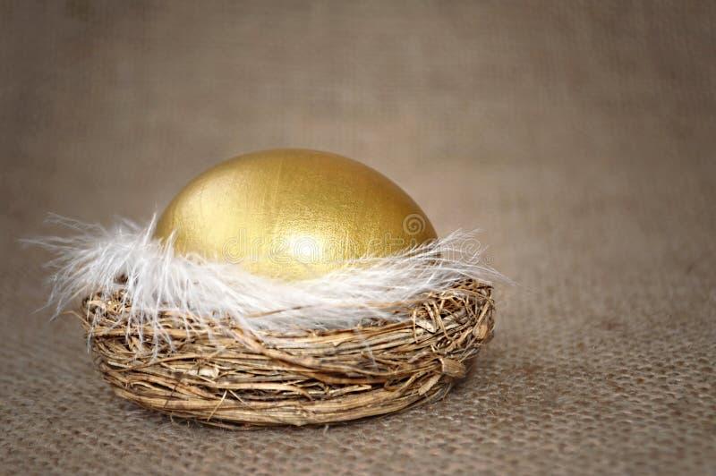 Golden Easter egg in the nest on canvas background. Happy Easter card: Golden Easter egg in the nest on canvas background royalty free stock images