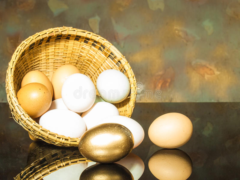 Golden egg. Still life photography eggs in an inverted basket. golden egg royalty free stock photo