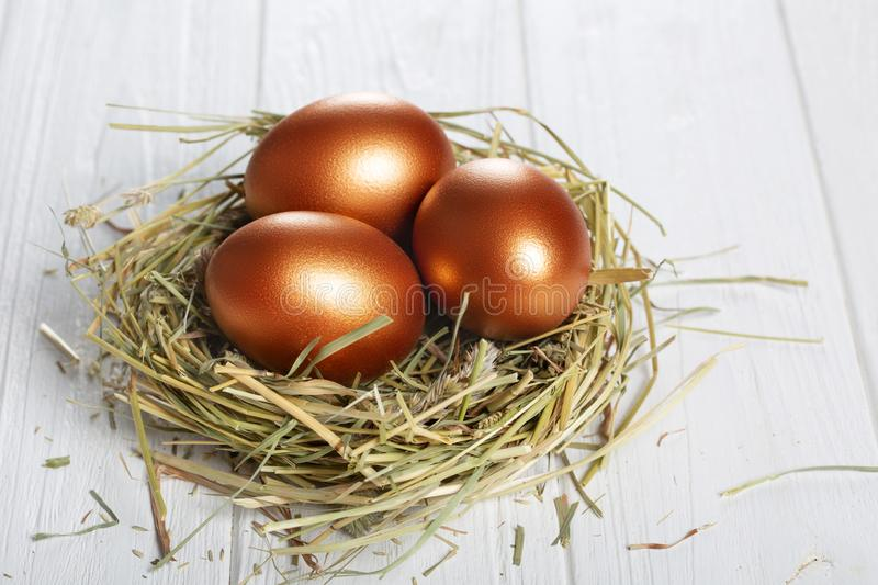 Golden eggs in a basket with hay on a white wooden . Easter composition. royalty free stock photo