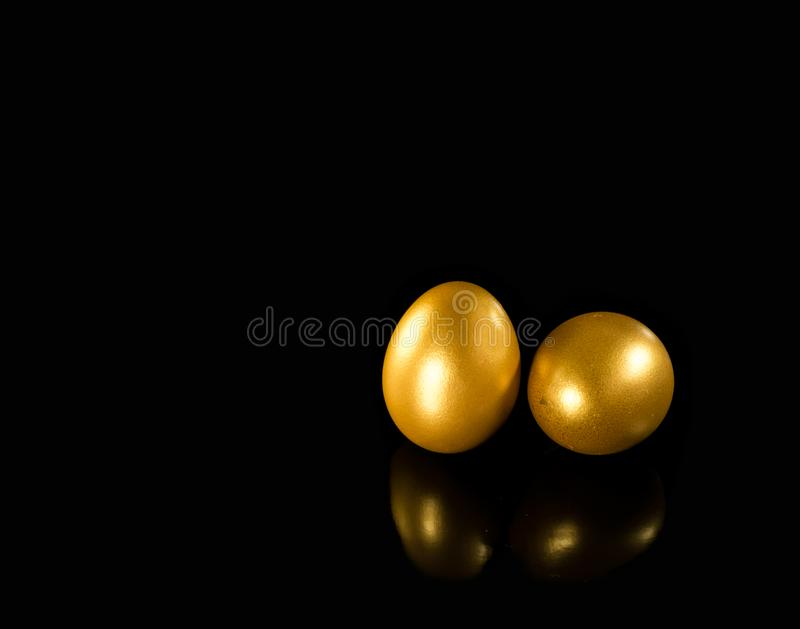 Golden eggs with copy space on black background royalty free stock image