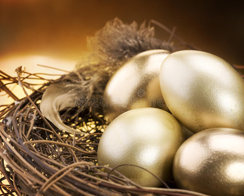 Golden Eggs In A Nest Stock Photos