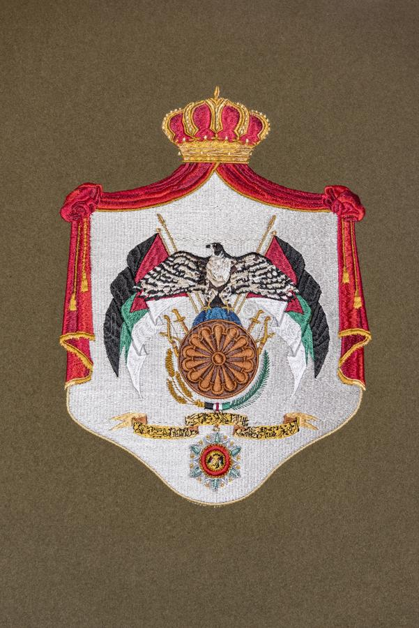 Jordan coat of arms. Golden embroidery of Jordan coat of arms on gray fabric stock illustration
