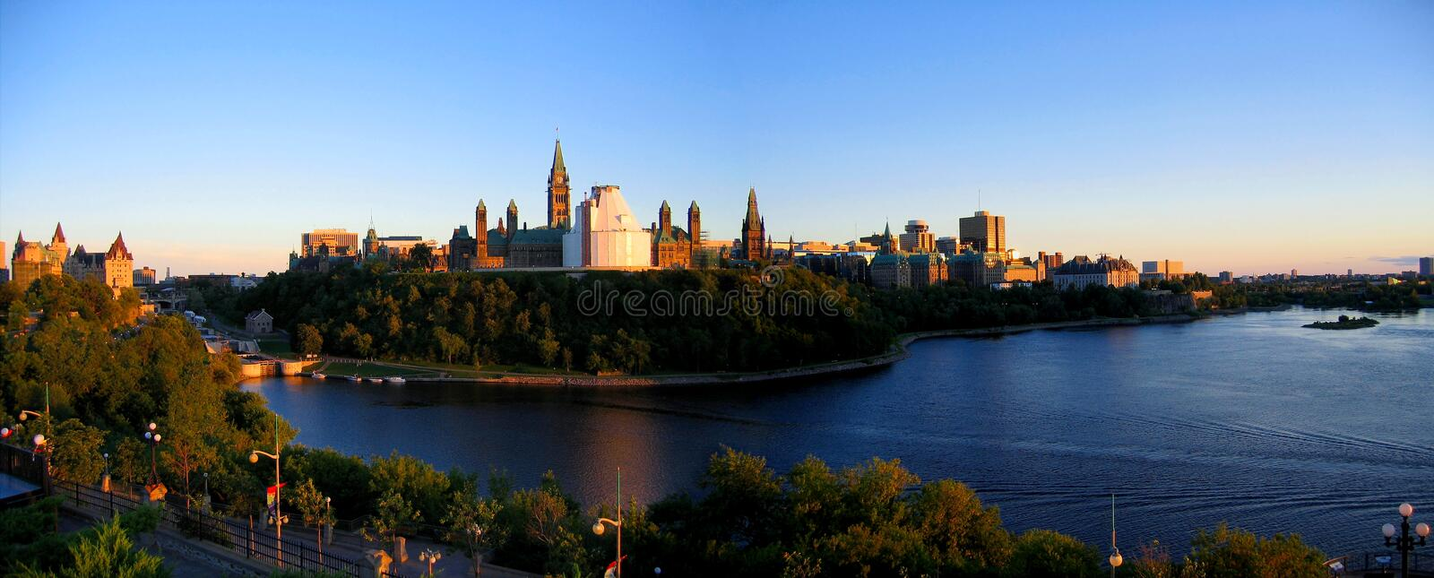 Golden Evening Light on Ottawa River and Parliament Hill, Ottawa, Ontario. Golden evening light shines on Parliament Hill rising steeply from the Ottawa River royalty free stock photography