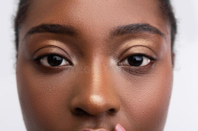Dark-skinned young woman with nice golden eyeshades. Golden eyeshades. Close up of young dark-skinned woman with nice golden eyeshades stock photos