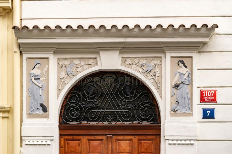 Ornamented front of a house in Prague with signs. Golden faces in a ornamented balcony in Prague royalty free stock image