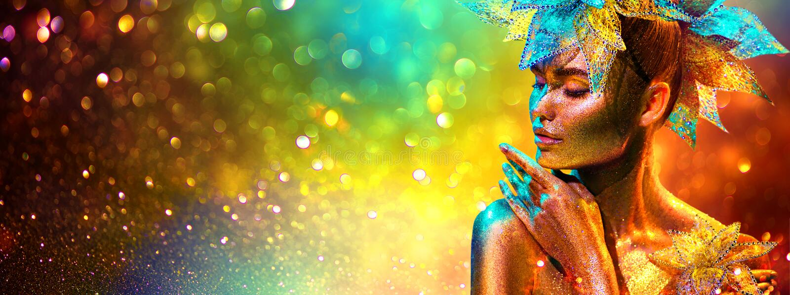 Golden Fashion model woman with bright golden sparkles on skin posing, fantasy flower, portrait of beautiful girl glowing makeup royalty free stock image