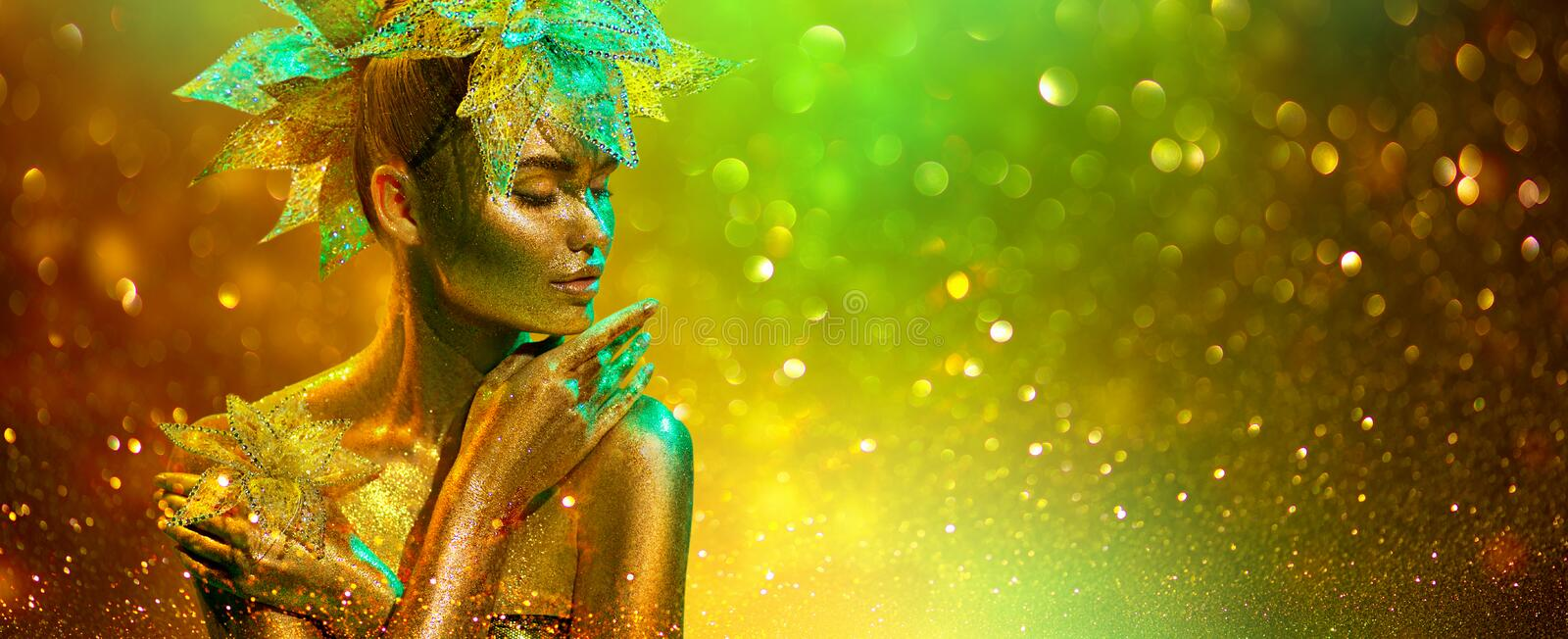 Golden Fashion model woman with bright golden sparkles on skin posing, fantasy flower, portrait of beautiful girl glowing makeup stock photography