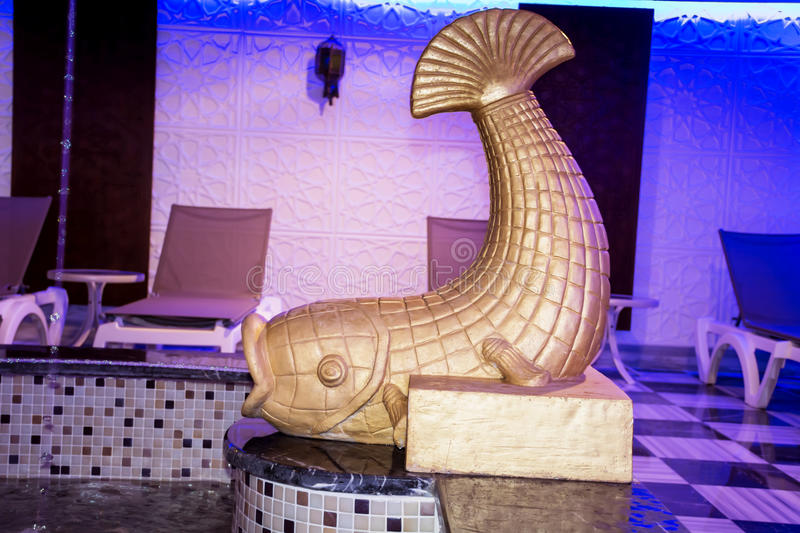 Golden Fish fountain for decoration in turkish bath hamam. Fish Stone fountain fragment on the pool stock photo