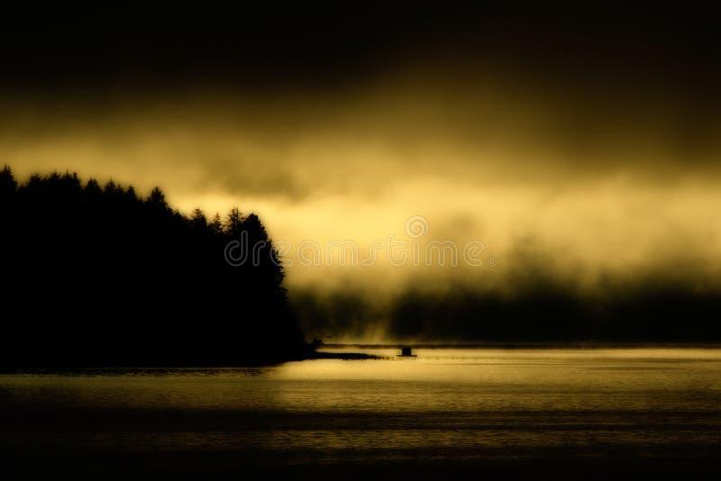 Golden Fog Sunrise on Siltcoos Lake, Oregon. Golden fog covered sunrise on Siltcoos Lake in Oregon stock photo