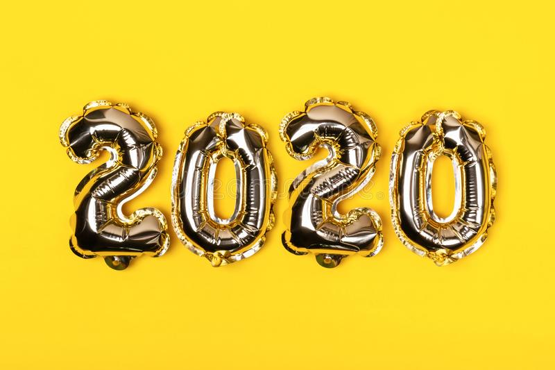 Golden foil balloons on yellow background. Inflatable numbers 2020. Christmas concept.  stock photo