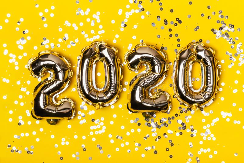 Golden foil balloons on yellow background with sparkles. Inflatable numbers 2020. Holiday Christmas concept.  stock photo