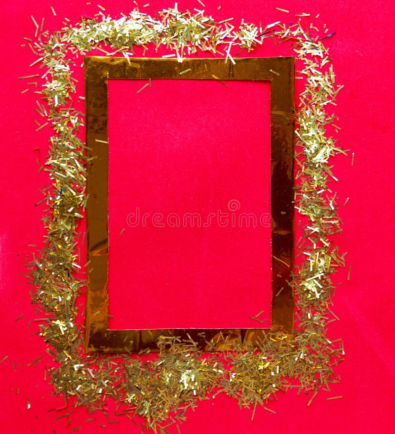 Golden frame with tinsel on bright red background. Copy space for the text. royalty free stock image