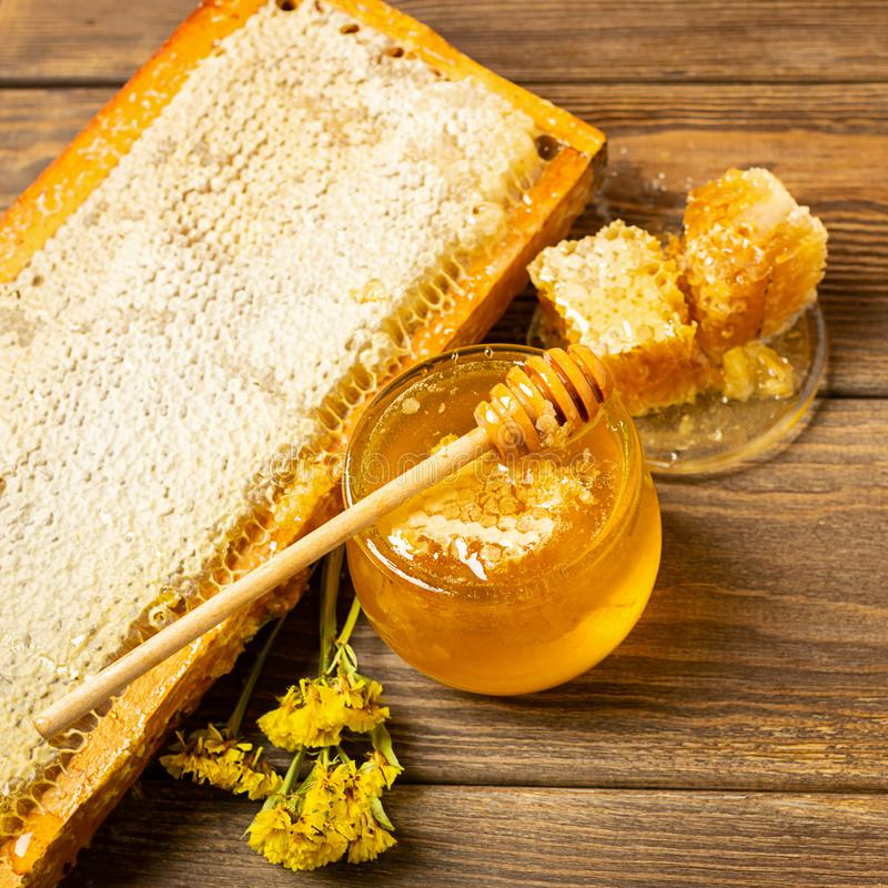 Golden fresh honey in a glass jar and honeycombs wooden table. The concept of natural products. Brown rustic background. royalty free stock photography