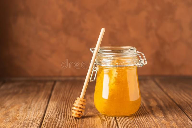 Golden fresh honey in a glass jar and a spoon of honey spoon on a brown background. The concept of natural products. royalty free stock photo