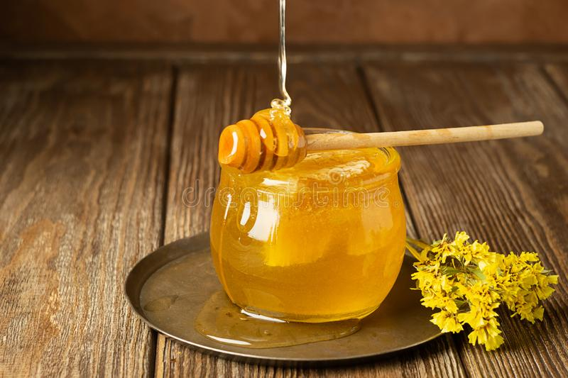 Golden fresh honey in a glass jar and a spoon of honey spoon on a brown background. The concept of natural products. stock photo