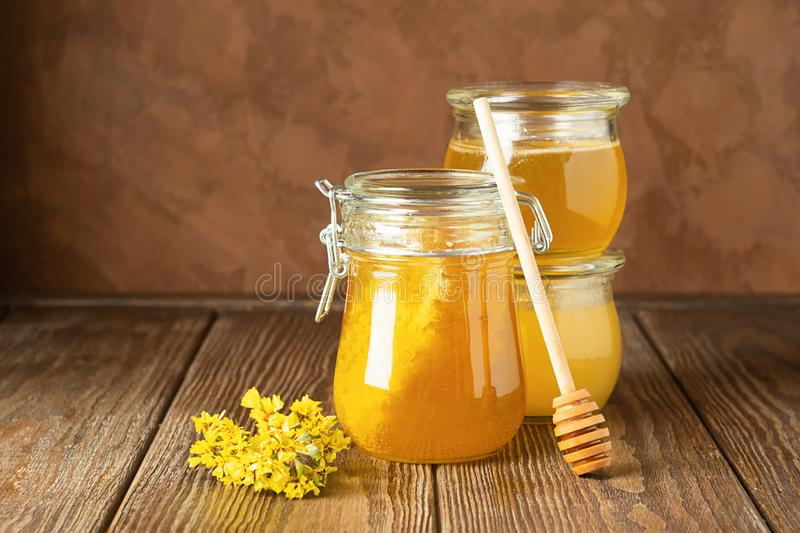 Golden fresh honey in various glass jars brown rustic background. The concept of natural products. Horizontal frame . royalty free stock photo