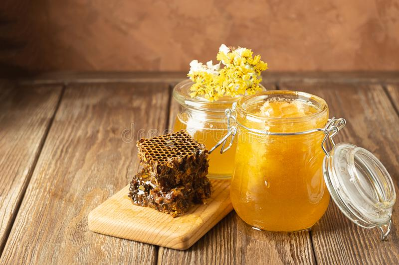 Golden fresh honey in various glass jars and honeycombs on wooden table. Organic food concept . Rustic brown background royalty free stock images