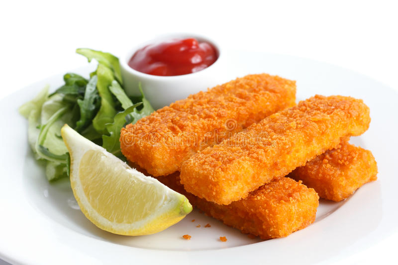 Golden fried fish fingers with lemon and tomato sauce stock image