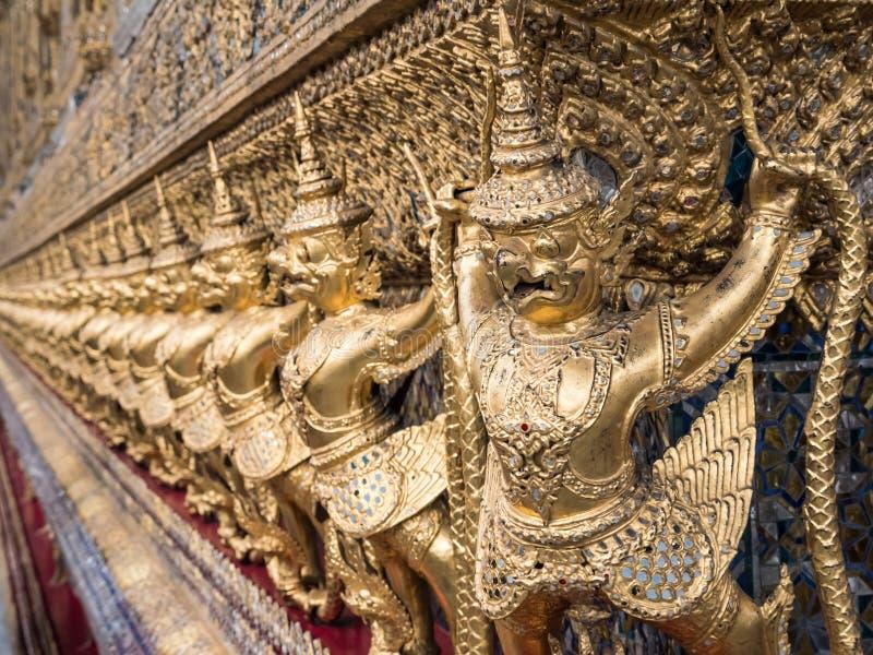 Golden garuda sculpture row around the church wall royalty free stock photo