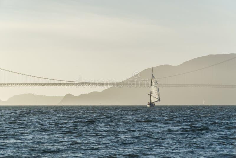 Golden Gate Bridge żeglowania jacht na zmierzchu krajobrazie obrazy royalty free