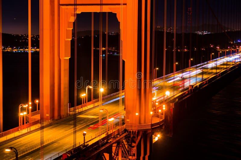 Golden gate bridge alla notte con le tracce della nave e dell'automobile immagini stock