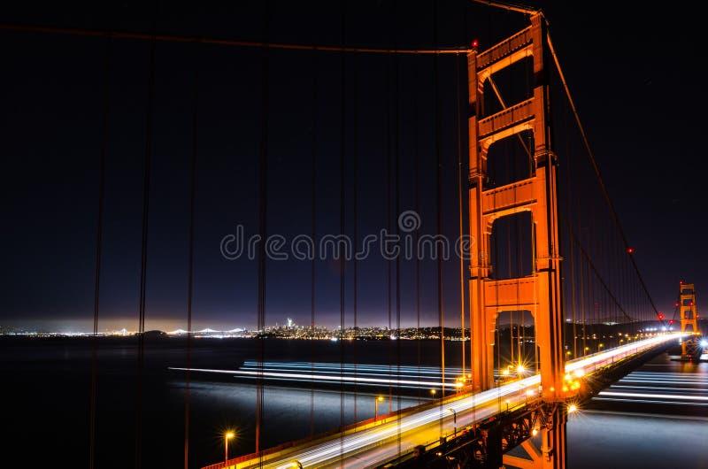 Golden gate bridge alla notte con le tracce della nave e dell'automobile fotografie stock