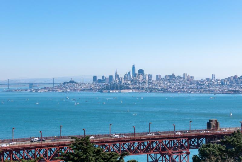 Golden Gate Bridge in California with skyline of downtown San Francisco and Oakland Bay Bridge stock photo