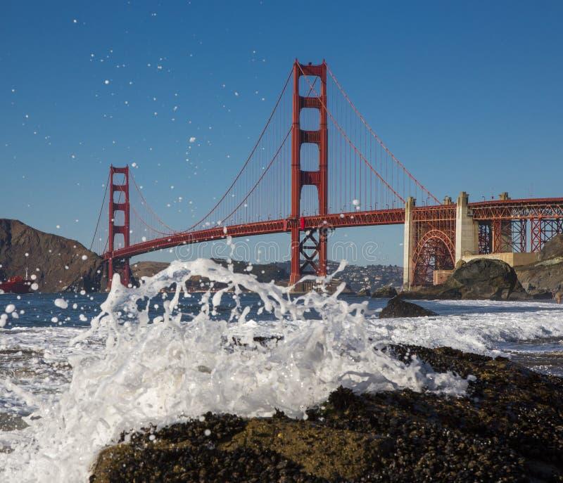 Golden Gate Bridge in California USA. Golden Gate Bridge in California and spray of the sea on the shore royalty free stock photos