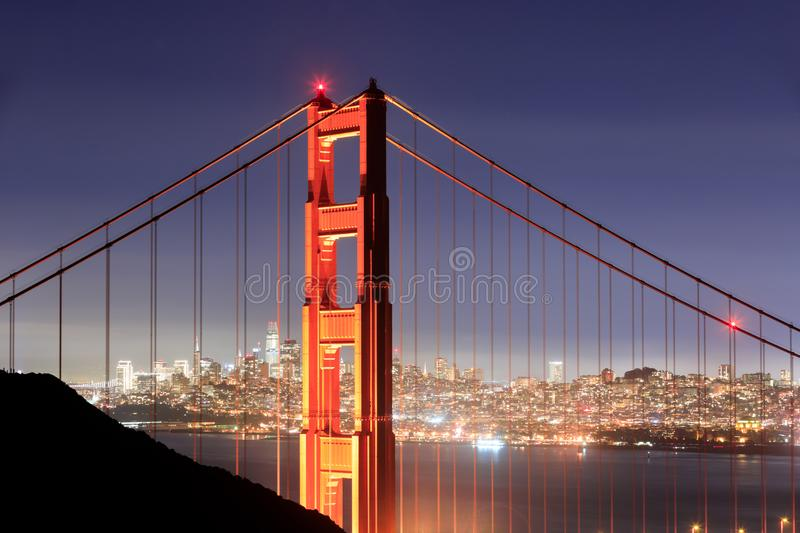 Golden Gate Bridge Close-up with San Francisco Skyline Background on a clear winter night. royalty free stock photography