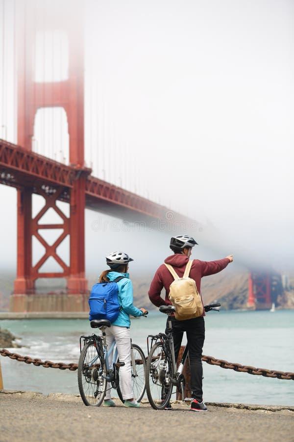 Golden gate bridge - coppia di ciclismo che fa un giro turistico fotografia stock libera da diritti