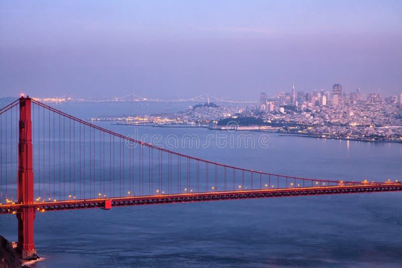 Golden gate bridge e skyline no crepúsculo imagem de stock royalty free